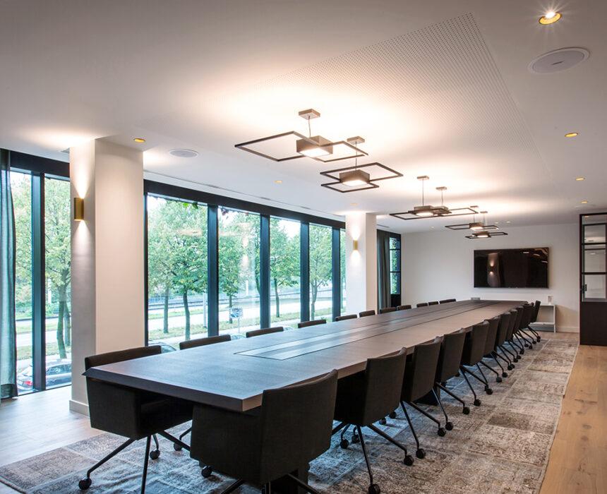 Een grote vergaderzaal met comfortabele meubilair in de boardroom van Greenhouse Antwerp